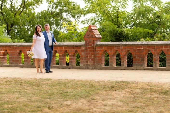 Hochzeitsreportage Tangermünde | Brautpaar steht an einer Mauer im Schlosspark